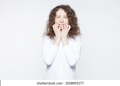 Scared young European woman looks with blue bugged eyes at camera, being afraid of something, keeps hands on mouth, looks in terror, isolated over white background. Emotional horrified female indoor.