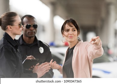 scared young female victim pointing by finger to policewoman and african american policeman writing in clipboard