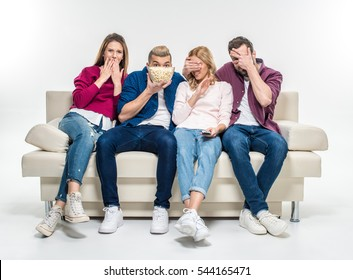Scared young friends sitting on couch with popcorn isolated on white