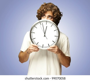 scared young man hidden behind a clock against a blue background
