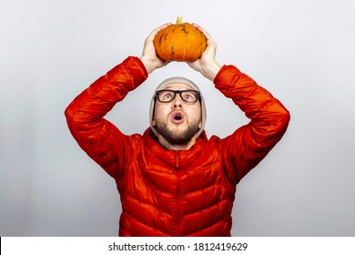 scared young man in a red jacket and hat, holds a pumpkin over his head and looks at the pumpkin on a light background. Concept of Halloween, celebration, autumn