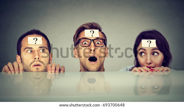 Scared young people two men and a woman with question mark hiding peeking from under the table