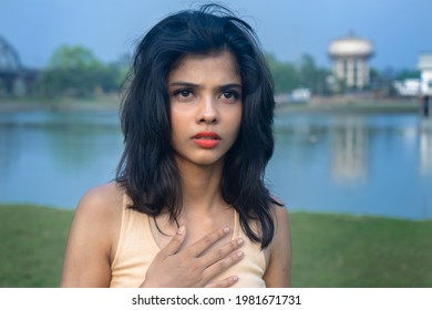 Scared young teenage girl looking aside, worrying about something, frightened young woman putting a hand on her chest | Close up of an Indian stressed girl feel terrified or afraid glancing at outdoor