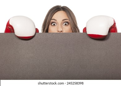 scared young woman with boxing gloves peeking behind empty board