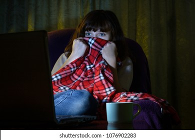 Scared young woman looks terrible movie at night on laptop