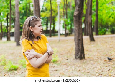 Scared young woman lost in the forest looking for a way out - Beautiful confused girl with brown hair and summer outfit walking alone in the woods while looking in the distance