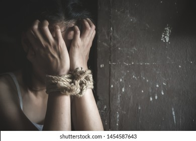 Scared young woman sitting in the corner of her bedroom, despair rape victim waiting for help,The concept of stopping violence against women and rape.