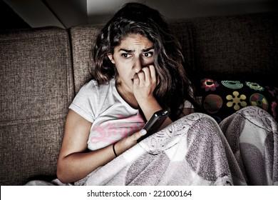 Schreckte junge Frau beim Fernsehen. Brunette Mädchen auf Sofa mit Fernbedienung sitzend