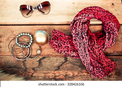 Scarf, bracelets, sunglasses and perfume on a wooden background