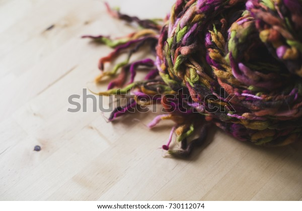 A scarf made of brown, pink, yellow, orange and green thread.