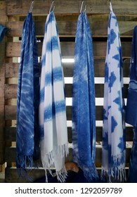 Scarf and shawl tie batik dyeing with mauhom indigo hanging on wooden wall in clothes shop for sale travelers people at market in Nonthaburi, Thailand