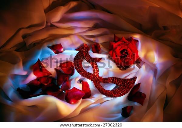 Scarlet mask and rose, alongside petals of rose. On fabric. Original illumination