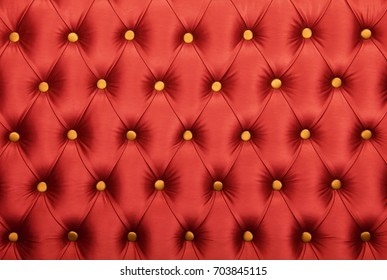 Scarlet ruby red capitone textile background with golden yellow buttons, retro Chesterfield style soft tufted fabric furniture upholstery diamond pattern decoration, close up