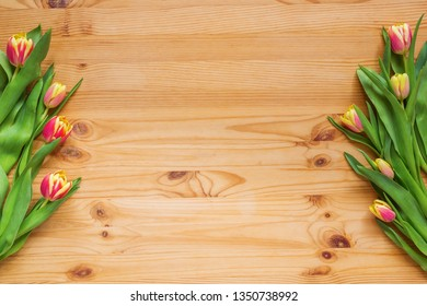 Scarlet tulips on the sides of the image, wooden background