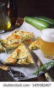 Scarpaccia, Italian cuisine. Slices of thin zucchini pie and mug of light beer