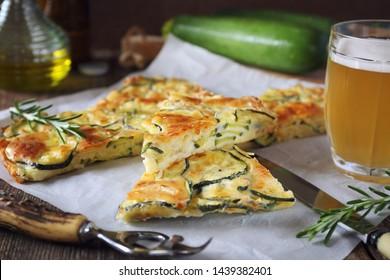 Scarpaccia, Italian cuisine. Thin zucchini pie and mug of light beer