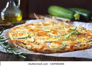 Scarpaccia, Italian cuisine. Thin zucchini pie and olive oil on wooden background