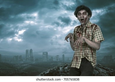 Scary asian zombie man with open mouth standing with dramatic sky background