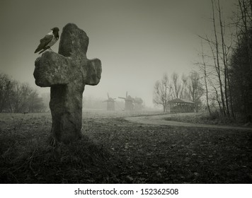 Scary background for Halloween. Old grave with a cross and the raven
