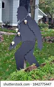 A Scary Black Creature with a chain around his neck and skulls hanging from the chain.