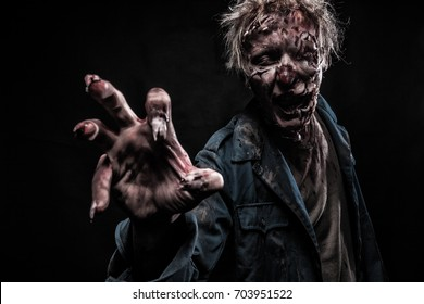 Scary Bloody Zombie Man with Glass in the Eye of Horror Halloween with a Hand and Broken Nails and Blood