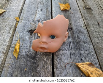 scary and broken doll face with one blue eye on a background of old wooden board with autumn leaves