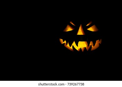 Scary candle lit Halloween pumpkin isolated on a black background.