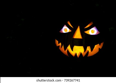 Scary candle lit Halloween pumpkin isolated on a black background with copy space.