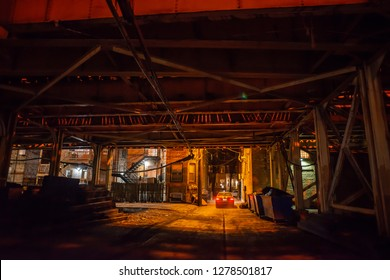 Scary Chicago alley under a vintage railroad bridge with a car at night