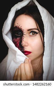 Scary close-up portrait of a woman with black eye and a cursed mark on her face on black background. Demonic nature in an innocent body concept