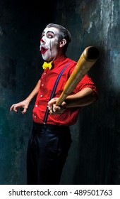 The scary clown and baseball-bat on dack background. Halloween concept