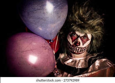 Scary Clown holding balloons in dark shadows