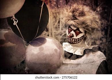 Scary clown holding dark balloons