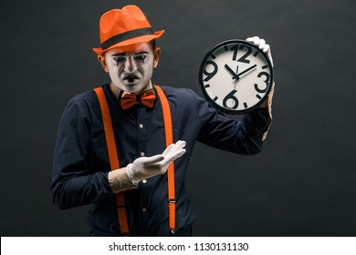 scary clown pantomime with a clock in his hands, on a dark background.