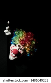 Scary clown peeping around the corner of a black wall. He is wearing a colored wig and sharp fangs.