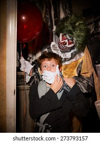 Scary Clown standing behind scared child in an opened closet with hand over his mouth