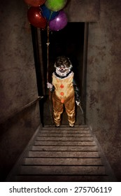 Scary Clown standing at the bottom of a stairway holding balloons and a knife
