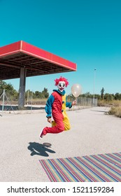 a scary clown wearing a colorful yellow, red and blue costume, holding a golden balloon in his hand, jumping in front of an abandoned filling station