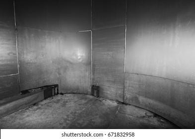 A scary cold futuristic metal sheet prison cell, with a harsh concrete floor. An black and white empty metal prison cell perfect for compositing.