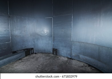 A scary cold  futuristic metal sheet prison cell, with a harsh concrete floor. An empty blue metal prison cell perfect for compositing.