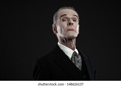 Scary count dracula in black suit. Pale head. Studio shot against black.
