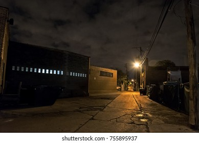 Scary dark city Chicago alley next to an urban warehouse.