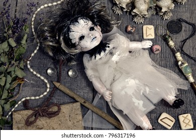 Scary doll in bride dress with runes and magic objects on planks. Occult, esoteric, divination and wicca concept. Halloween vintage background
