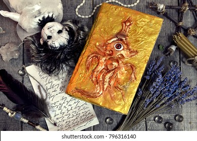 Scary doll with old magic book, manuscript with text and lavender bunch on planks. Occult, esoteric, divination and wicca concept. No foreign text, all symbols on pages are fantasy, imaginary ones.