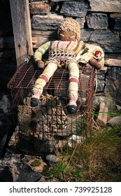 Scary Doll on Cage with Sheep Skull Under Arm