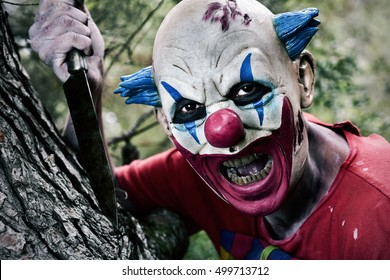 a scary evil clown with a big knife in his hand in the woods