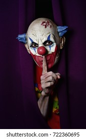 a scary evil clown peering out from a purple stage curtain, with his forefinger in front of his lips, asking for silence