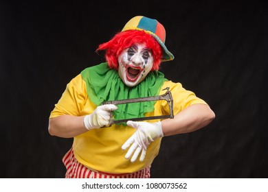 Scary evil clown with an ugly smile and saw on a black backgroun