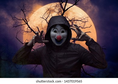 Scary evil clown wear jacket standing over dead tree, full moon and spooky cloudy sky, Halloween mystery concept