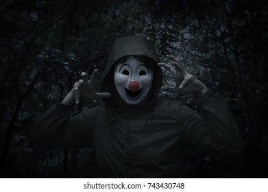 Scary evil clown wear jacket over spooky tree and forest at night time, Halloween concept